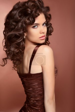 Healthy hair. Beautiful brunette young  woman with long curly ha