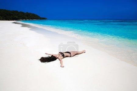 Enjoyment. Beautiful brunette lying On Tropical Beach. Sexy biki