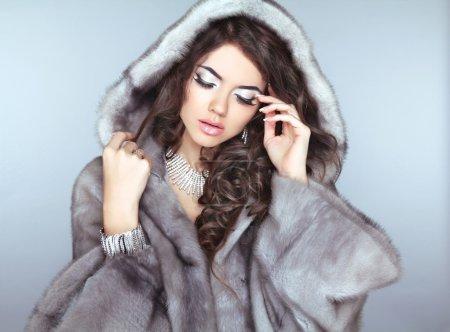 Photo pour Beauté mode modèle fille en manteau de fourrure, belle femme brune aux cheveux ondulé et maquillage. - image libre de droit