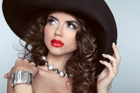 Beauty brunette woman with red lips, wavy hair, fashion jewelry.