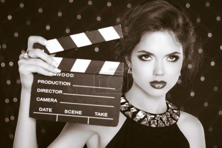 Retro casting tests, woman holding cinema clap. Super star model
