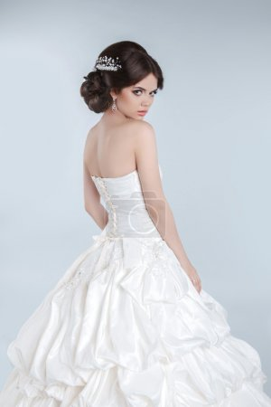 Beauty Fashion young bride model posing in wedding dress with ha