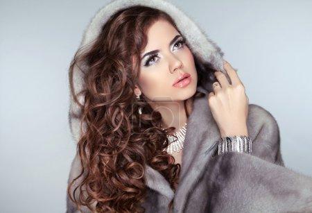 Fashion beautiful woman posing in fur coat. Winter Girl Model in