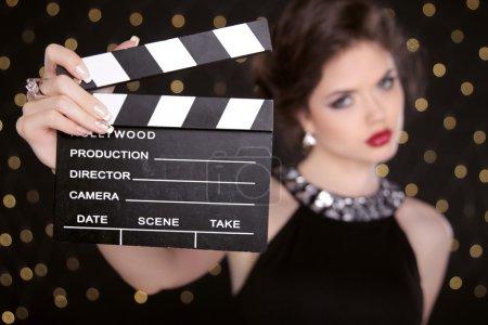 Beautiful brunette woman model holding film clap board cinema. F