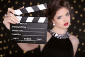 Beautiful brunette woman model holding film clap board cinema. F