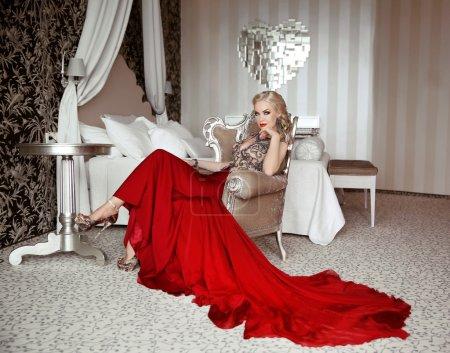 Photo pour Belle femme adulte dans la robe rouge de mode s'asseyant sur le fauteuil moderne à l'appartement intérieur luxueux avec des meubles. - image libre de droit