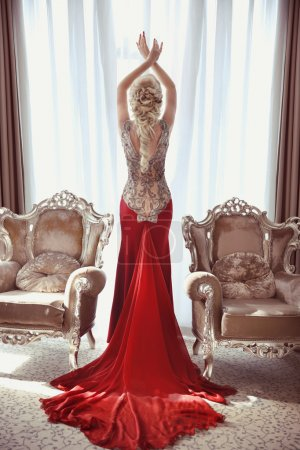 Indoor full length portrait of elegant blond woman in red gown w
