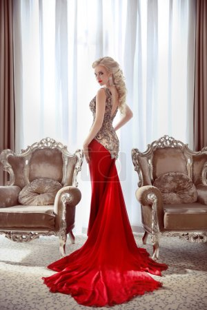 Photo for Elegant lady. Beautiful blond woman model in fashion dress with long red train posing between two modern armchairs in front of window at interior. - Royalty Free Image