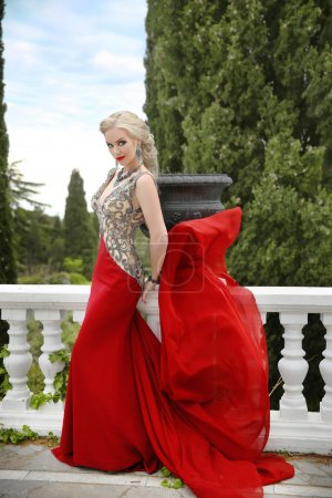 Woman in red waving dress. Fashion blond model in blowing gown o