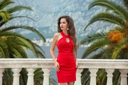 Beautiful young sexy brunette girl in red dress posing on Balcon