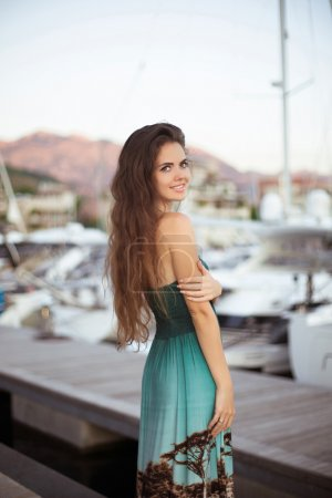 Beautiful smiling brunette girl with long hair posing by yachts