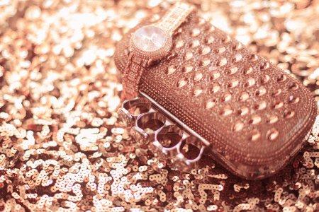 Luxury women accessories. wristwatch and purse, on golden sequin