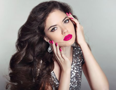 Photo for Makeup. Beautiful girl portrait. Long hair. Brunette fashion woman with red lips, manicured nails, healthy curly shiny hairstyle posing on studio background. - Royalty Free Image