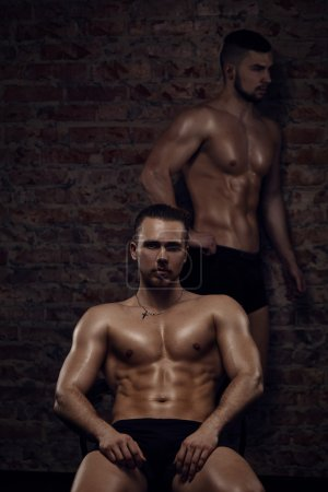 Photo for Young muscular men near red brick wall. One is sitting another is standing - Royalty Free Image
