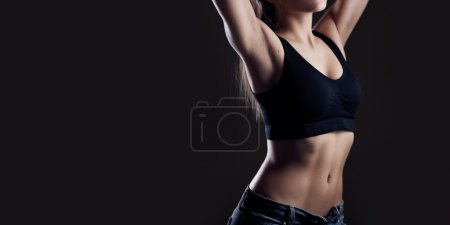 Photo for Young attractive sexy fit brunette on dark background - Royalty Free Image