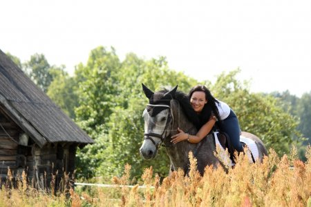 Portrait of beautiful woman on horse near the barn