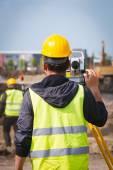 Surveyor inženýr pracovník tvorby, měření s teodolit zařízení na staveništi