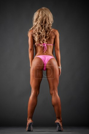 Photo for Athletic woman in pink bikini showing buttocks on dark background - Royalty Free Image