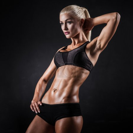 Photo for Beautiful athletic woman showing muscles on dark background - Royalty Free Image