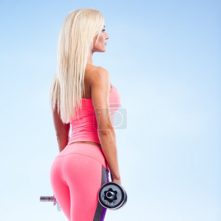 Photo for Beautiful fitness model posing with dumbbells on blue background - Royalty Free Image