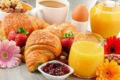 Snídaně sestávající z croissanty, kávu, ovoce, džus