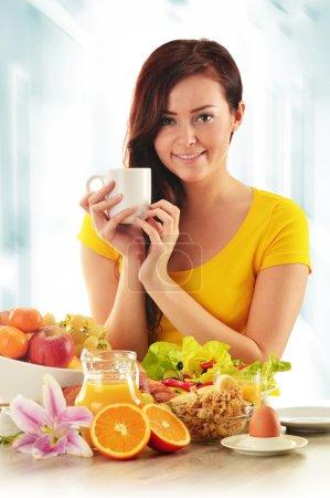 Photo pour Une jeune femme qui prend son petit déjeuner. Régime alimentaire équilibré - image libre de droit