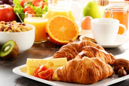 Photo for Breakfast consisting of fruits, orange juice, coffee, honey, bread and egg. Balanced diet. - Royalty Free Image