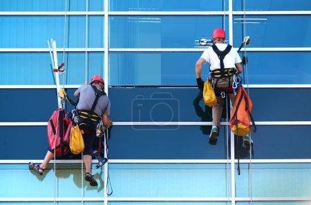 Foto de Dos trabajadores de la construcción que trabajan en altura en un rascacielos comercial moderno . - Imagen libre de derechos