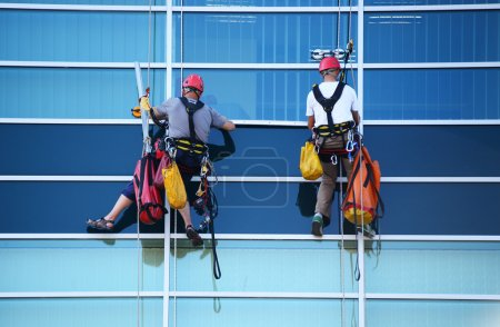 Two construction workers working at height on skyscraper