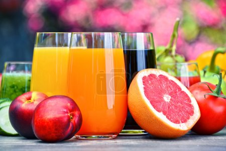 Photo for Glasses with fresh organic detox juices in the garden - Royalty Free Image