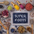 Super foods in spoons and bowls on a wooden backgr...