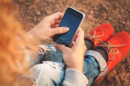 Photo pour Femme hipster jeune belle à l'aide de téléphone intelligent à la plage - image libre de droit