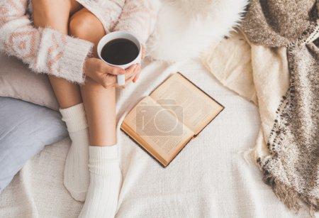 Foto de Foto suave de la mujer en la cama con el libro viejo y taza de café en las manos, punto de vista superior - Imagen libre de derechos
