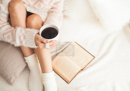 Soft photo of woman on the bed with old book and c...