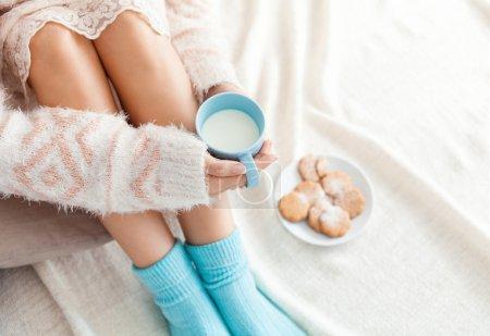 Foto de Foto suave de mujer en la cama con la taza de leche en las manos, punto de vista superior - Imagen libre de derechos