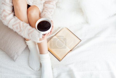 Foto de Foto suave de la mujer en la cama con el libro viejo y taza de café, top Mirador - Imagen libre de derechos