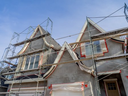 Photo pour Échafaudages entourant la maison après l'application de stuc extérieur lisse, mais avant la peinture. Maison située à Calgary . - image libre de droit