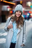 Beautiful smiling woman walking on the New York City street wearing casual style clothes