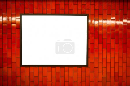 Advertisement empty poster space frame on the brick red wall on subway station