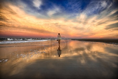 young woman walking on the beach near the ocean and walking away at the sunset