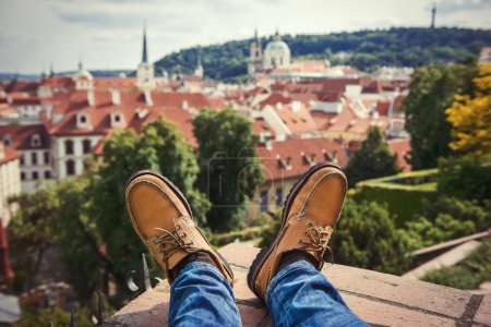 Men`s feet wearing brownleather shoes relaxing on the rooftop in old town of Prague