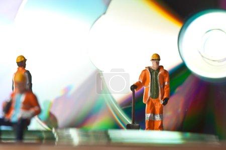 Photo pour Travailleurs miniatures avec CD en action dans diverses situations - image libre de droit