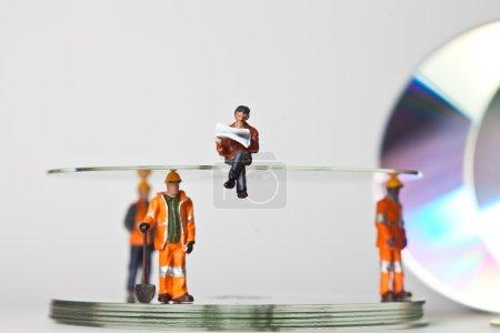 Photo pour Travailleurs miniatures en action avec des CD dans diverses situations - image libre de droit