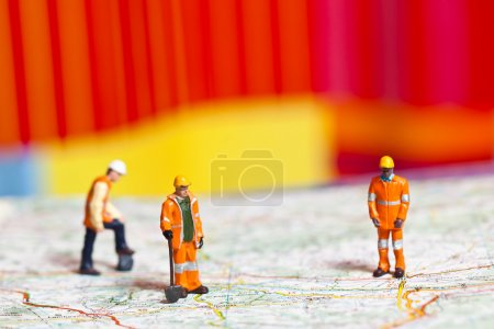 Miniature workers in action on a roadmap