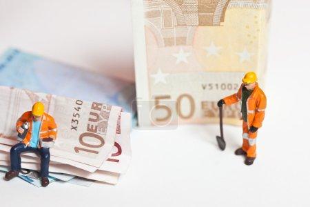 Photo pour Travailleurs miniatures en action avec des billets en euros dans diverses situations - image libre de droit