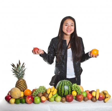 Photo for Asian girl with different fruits stacked together - Royalty Free Image