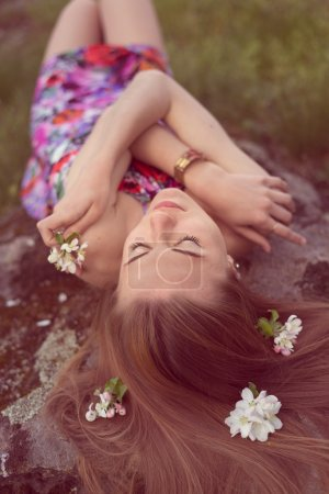 close up portrait of beautiful blonde woman young cute girl laying on stone with flowers in her hair closing eyes dreaming outdoors image
