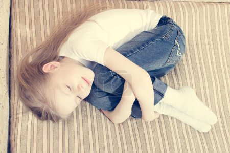 Blond kid laying on bed hugging herself