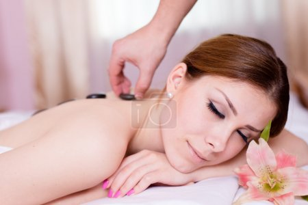 Spa relaxing: beautiful young attractive blond woman having fun enjoying relaxation during stone therapy massage & aromatherapy eyes closed lying on white bed background closeup portrait