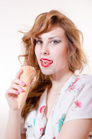 Photo for Beautiful young pinup lady having fun enjoying eating ice cream cone, looking at camera isolated over white copy space background - Royalty Free Image